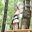 Stock Photo: Young girl balancing on rope in adventure climbing high wire par