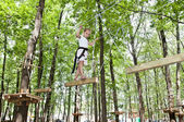 Young girl balancing on rope in adventure climbing high wire par — Stock Photo