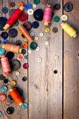 Spoelen van threads en knoppen op oude houten tafel — Stockfoto