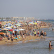 Mediterranean beach crowded with tourists - Stock Photo