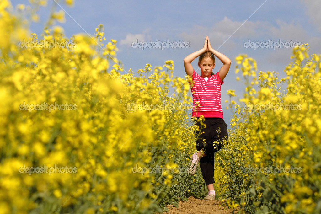 Young girl practicing yoga in the nature trail in the fields — Stock Photo #10797828