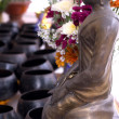 Buddha residing over the collection pots — Stock Photo