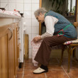 Old woman by cooking - waiting — Stock Photo