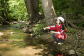 Little girl by forest creek — Stock Photo