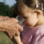 handen van oude vrouw en het kind op drinken — Stockfoto