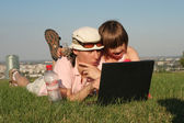 Mother and daughter at work on the notebook in park — Fotografia Stock