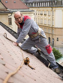 Man at work and calling on the roof — Stock Photo