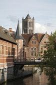 Gent - igreja da torre de são nicolau e o canal com as casas de tijolo típico. — Foto Stock