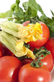 Red tomatoes with squash blossoms and basil — Stock Photo