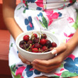 The young girl holding a plate of sweet cherry — Stock Photo