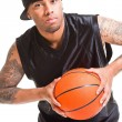 Stock Photo: Studio portrait of basketball player wearing black cap standing and holding ball isolated on white.