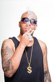 Hip hop urban gangster black man wearing dark shirt and bling bling isolated on white. Smoking cigarette. Looking confident. Cool guy. Studio shot. — Stock Photo