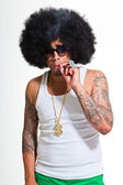 Hip hop urban black man retro afro hair wearing white shirt and bling bling isolated on white. Smoking cigarette. Looking confident. Cool guy. Studio shot. — Stock Photo