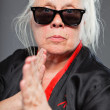 Senior woman with long grey hair wearing black and red kimono and black sunglasses. Doing karate moves. Studio shot isolated on grey background. — Stock Photo