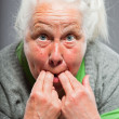 Senior woman whistling with her fingers. Acting young. Studio shot isolated on grey background. — Stock Photo