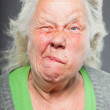 Senior woman white grey hair with expressive emotional face and hands. Studio shot isolated on grey background. — Stock Photo #11240596