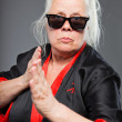 Senior woman with long grey hair wearing black and red kimono and black sunglasses. Doing karate moves. Studio shot isolated on grey background. — Stock Photo #11240642