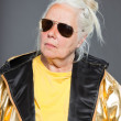 Cool senior woman wearing golden jacket. Long grey hair. Sunglasses. Studio shot. Isolated. — Stock Photo