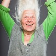 Senior woman holding hands in her hair. Spiritual looking. Studio shot isolated on grey background. — Stock Photo #11241106
