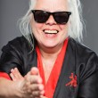 Stock Photo: Senior womwith long grey hair wearing black and red kimono and black sunglasses. Doing karate moves. Studio shot isolated on grey background.