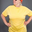 Funny and happy senior woman wearing yellow shirt and orange hat and sunglasses. Cool and hip. Studio shot isolated on grey. — Stock Photo #11241477
