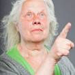 Senior woman white grey hair doing spiritual poses. Expressive face and hands. Studio shot isolated on grey background. — Stock Photo