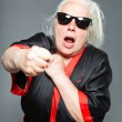 Senior woman with long grey hair wearing black and red kimono and black sunglasses. Doing karate moves. Studio shot isolated on grey background. — Stock Photo #11241514