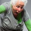 Stock Photo: Funny expressive senior woman. Acting young. Studio shot isolated on grey background.