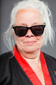 Senior woman with long grey hair wearing black and red kimono and black sunglasses. Cool looking. Studio shot isolated on grey background. — Stock Photo