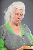 読書を年配の女性の肖像画スタジオ。スタジオ撮影に分離の灰色の背景. — ストック写真