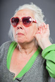 Senior woman with sunglasses deaf. Bad hearing. Hip and cool looking. Studio shot. Isolated on grey background. — Stock Photo