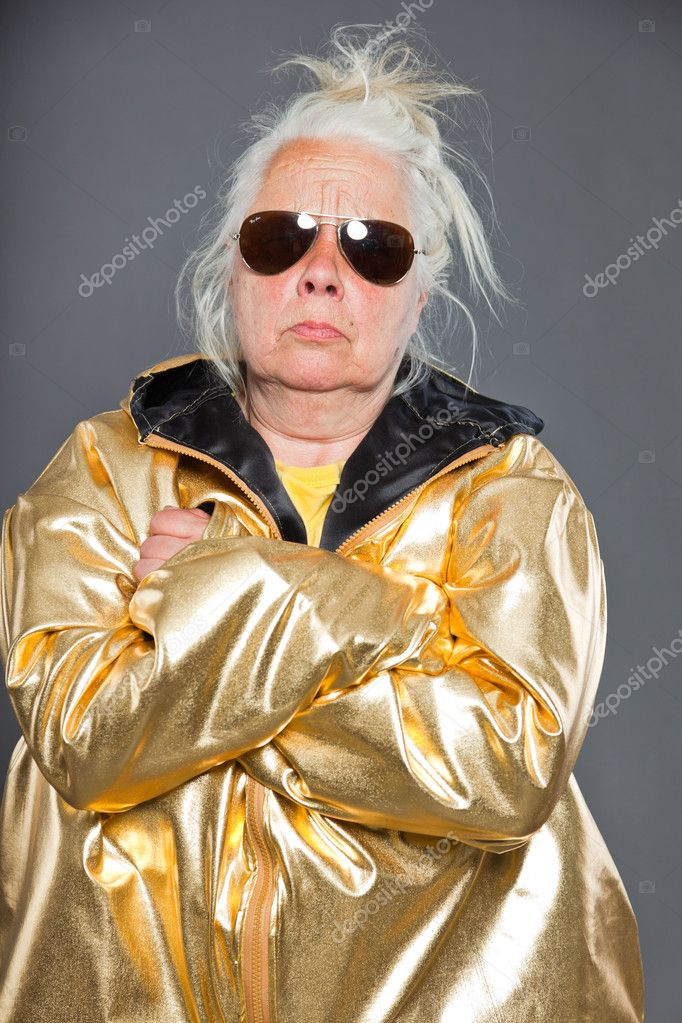 Cool senior woman wearing golden jacket. Long grey hair. Sunglasses. Studio shot. Isolated. — Stock Photo #11242012