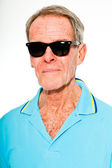 Expressive good looking senior man casual summer dressed against white wall. Wearing sunglasses. Happy, funny and characteristic. Isolated. Studio shot. — Stock Photo