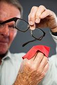 Expresivo apuesto hombre senior contra la pared gris. limpieza de sus lentes. divertido y característico. bien vestida. estudio de tiro. — Foto de Stock