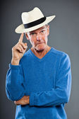 Expressive good looking senior man against grey wall. Wearing hat. Funny and characteristic. Well dressed. Blue sweater. Studio shot. — Stock Photo