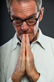Expressive good looking senior man with glasses against grey wall. Hands praying. Spiritual and characteristic. Well dressed. Studio shot. — Stock Photo