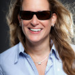 Royalty-Free Stock Photo: Pretty woman long blond hair wearing sunglasses and light blue shirt. Isolated on grey background. Studio shot.