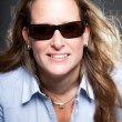 Pretty woman long blond hair wearing sunglasses and light blue shirt. Isolated on grey background. Studio shot. — Stock Photo #11371522