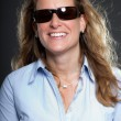Pretty woman long blond hair wearing sunglasses and light blue shirt. Isolated on grey background. Studio shot. — Stock Photo