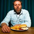 Man with beard eating fast food meal. Enjoying french fries and a hamburger. — Stock Photo #11597573
