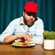 Man with beard eating fast food meal. Enjoying french fries and a hamburger. Trucker with red cap. — Stock Photo #11597579