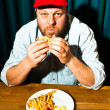 Man with beard eating fast food meal. Enjoying french fries and a hamburger. Trucker with red cap. — Stock Photo #11597580
