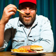 Man with beard eating fast food meal. Enjoying french fries and a hamburger. Trucker with red cap. — Stock Photo #11597583