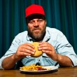 Man with beard eating fast food meal. Enjoying french fries and a hamburger. Trucker with red cap. — Stock Photo #11597591