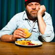 Man with beard eating fast food meal. Enjoying french fries and a hamburger. Trucker with red cap. — Stock Photo #11597592