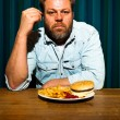 Mwith beard eating fast food meal. Enjoying french fries and hamburger. — Stock Photo #11597596