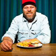 Mwith beard eating fast food meal. Enjoying french fries and hamburger. Trucker with red cap. — Stock Photo #11597617