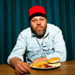 Man with beard eating fast food meal. Enjoying french fries and a hamburger. Trucker with red cap. — Stock Photo #11597621