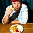 Man with beard eating fast food meal. Enjoying french fries and a hamburger. Trucker with red cap. — Stock Photo #11597626