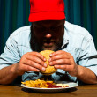 Man with beard eating fast food meal. Enjoying french fries and a hamburger. Trucker with red cap. — Stock Photo